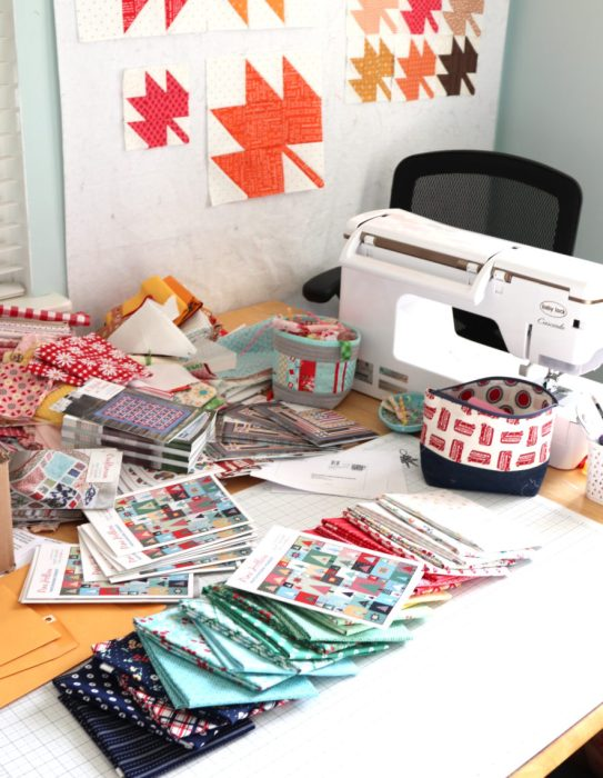 Delayed Pine Hollow Pattern by popular quilting blog, Diary of a Quilter: image of a sewing table with various fabrics and a pine hollow pattern on it.