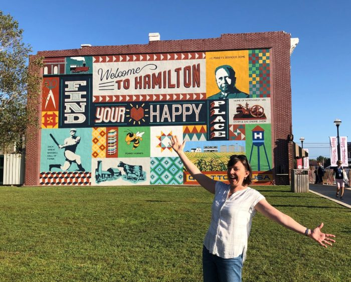 Birthday Bash at Missouri Star Quilt Company by popular quilting blog, Diary of a Quilter: image of a woman standing in front of the Welcome to Hamilton sign.