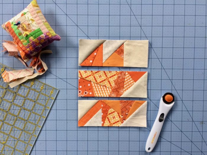 Scrappy Maple Leaf Quilt Pattern Tutorial by guest writer Leila Gardunia by popular quilting blog, Diary of a Quilter: image of scrappy maple leaf quilt blocks on a cutting board next to a rotary cutter.