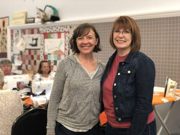 Days For Girls by popular quilting blog, Diary of a Quilter: image of two women standing together in a fabric store.