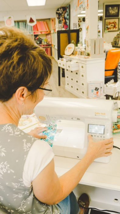 Shop Local - My Girlfriend's Quilt Shoppe + Giveaway by popular Utah quilting blog, Diary of a Quilter: image of a woman sitting at a sewing machine.