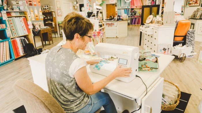 Shop Local - My Girlfriend's Quilt Shoppe + Giveaway by popular Utah quilting blog, Diary of a Quilter: image of a woman sitting at a sewing machine inside My Girlfriend's Quilt Shoppe.