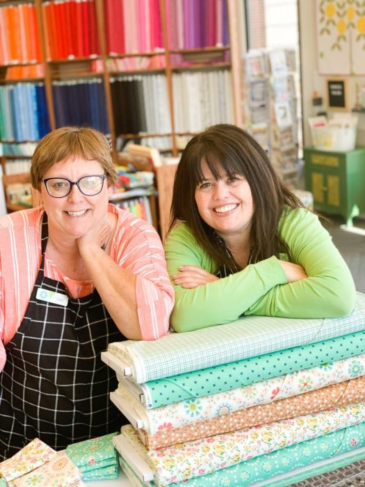 Shop Local - My Girlfriend's Quilt Shoppe + Giveaway by popular Utah quilting blog, Diary of a Quilter: image of two women leaning on top of fabric bolts inside My Girlfriend's Quilt Shoppe.