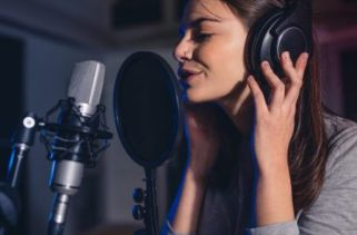 Por que cantores e atores usam fones de ouvido no estúdio de gravação?