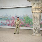 A worker in Yonggwang (Glory) Station, built in 1987.  Behind him is a mural of Pyongyang city with the Tadedong River and willow blossoms in front.