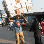 Superman carrying used food oil drums.