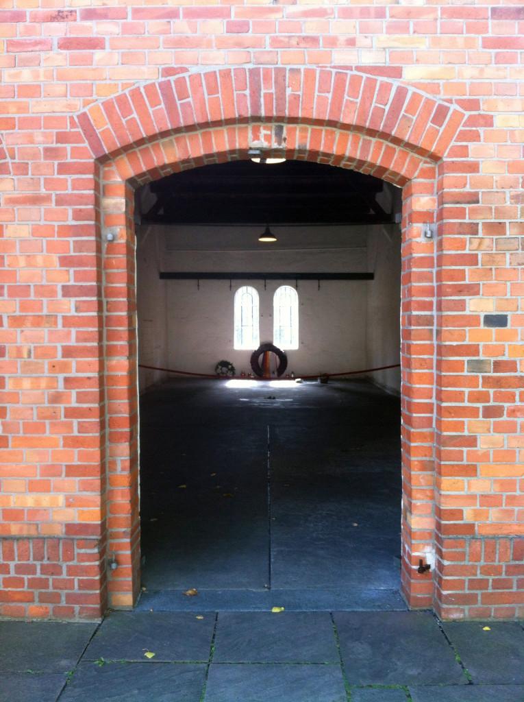 Ein Raum mit zwei halbrunden Fenstern hinter einem Backstein-Eingang.