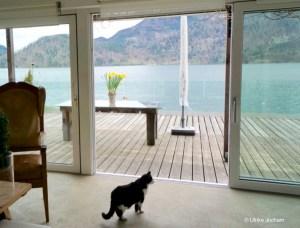 Eine Hebe-Schiebetür mit Nullschwelle verbessert die Ästhetik nicht nur von Türen sondern von ganzen Räumen und deren Ausblicke, ein Foto von der Frau Nullschwellle mit Blick auf einen wunderschönen Bergsee