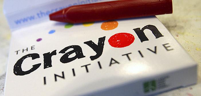 crayon de cire rouge sur le dessus d'une petite boîte avec le logo Initiative Crayon
