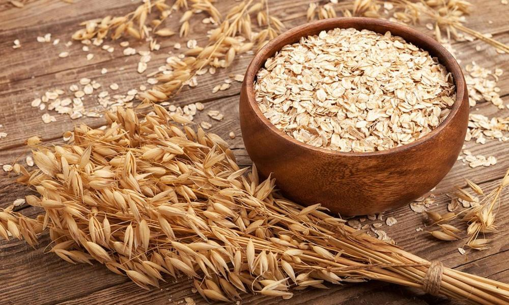 medium resolution of oat flakes rolled oats in wooden bowl in front of oat ears
