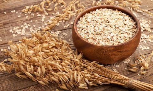 small resolution of oat flakes rolled oats in wooden bowl in front of oat ears