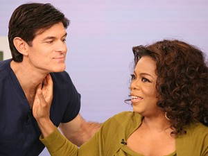 Picture of Oprah Winfrey checking the pulse on the throat of Dr. Oz