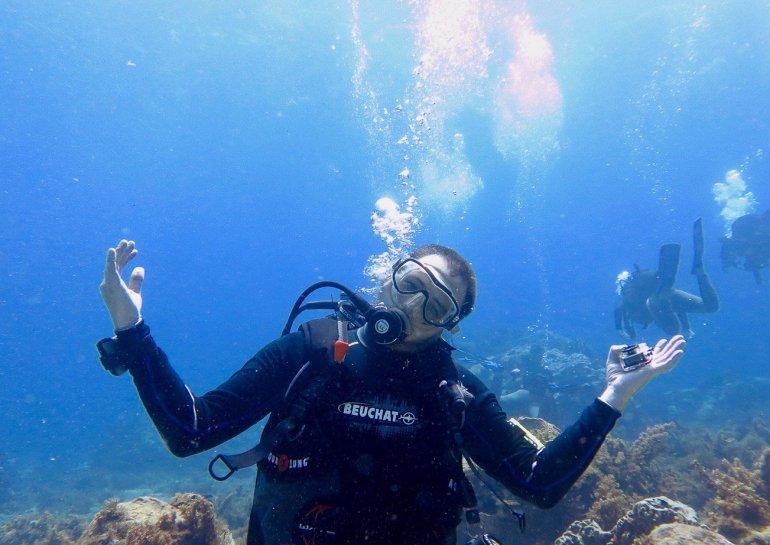 Un plongeur sourit en regardant l'objectif