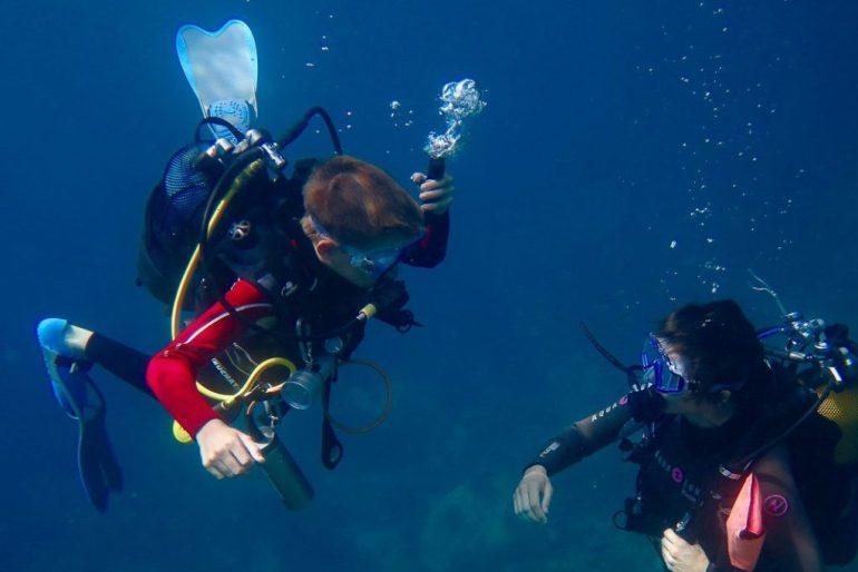 Un enfant fait de la plongée avec une monitrice