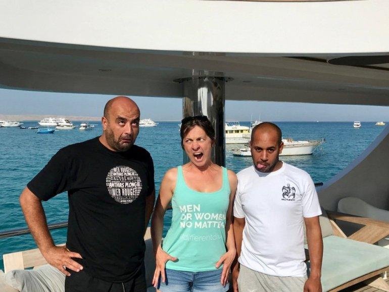 Deux plongeurs et une plongeuse font des grimaces sur un bateau de croisière de plongée