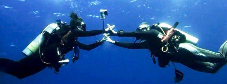Un couple de plongeurs se donnent la main sous l'eau en étant allé plonger en couple