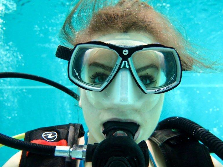 Une femme regarde à travers son masque de plongée