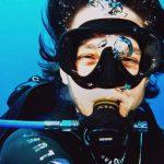 Regard d'une plongeuse souriante à travers son masque