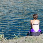 Une femme de dos regarde un plan d'eau après son accident de plongée