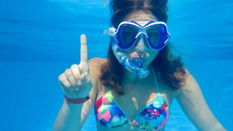 Une jeune fille montre un un avec ses doigts pour expliquer le briefing de plongée