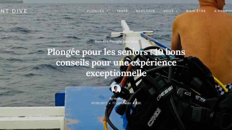 Un plongeur est assis sur un bateau et regarde a mer