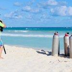 Un enfant regarde la mer près de bouteilles de plongée
