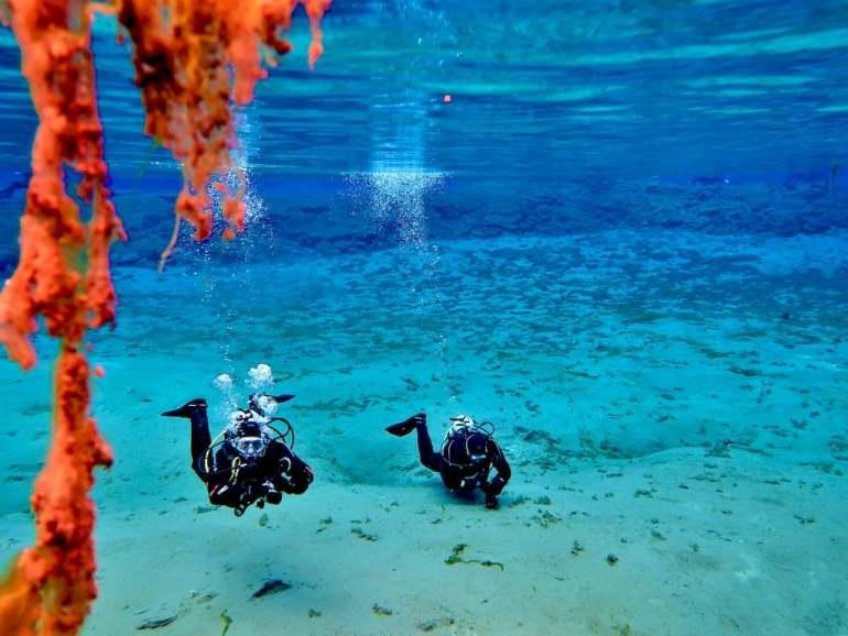 Deux plongeurs évoluent dans le lac à la sortie de la faille de Silfra