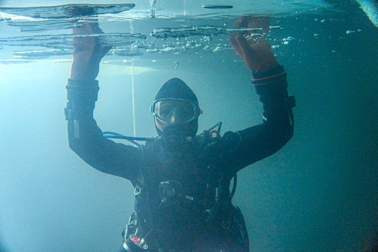 Une plongeuse se tient sous la glace