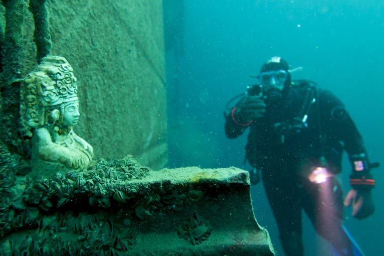 Un plongeur film une statuette dans la carrière de Vodelée