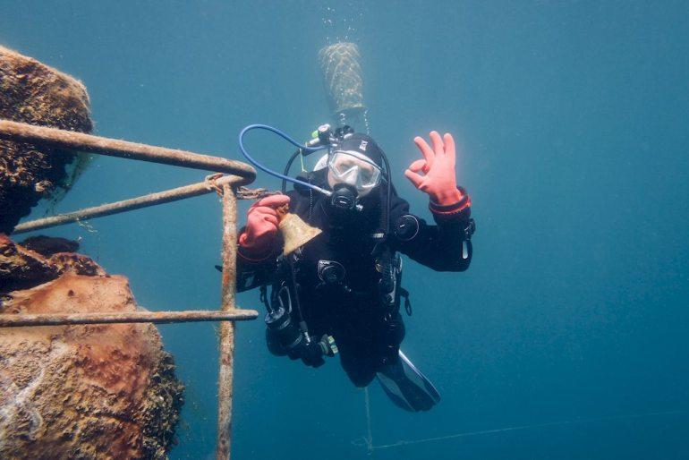 Hélène tient une cloche sous l'eau annonçant la fin de la plongée dans la carrière de Vodelée