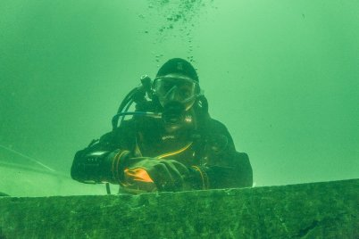 Hélène sous l'eau se tient les bras croisées