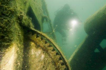 Un plongeur éclaire des machineries dans l'eau de la carrière de Rochefontaine
