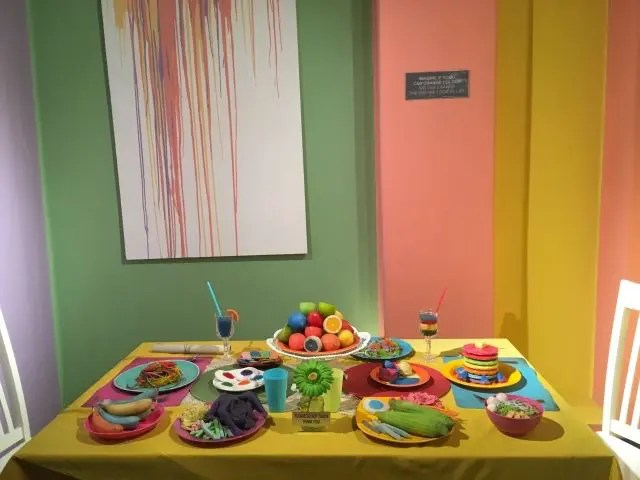 Table of unusual coloured food at Wonderfood Penang. Bananas are blue and pink, pasta is yellow and purple.