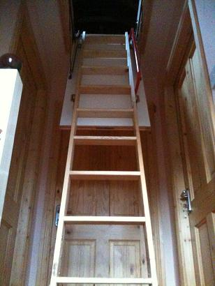 Picture of a very cool wooden ladder stretching up to the large opening for the attick.