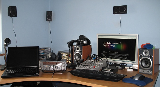 A picture of my desk full of technology. You can see the mixer, laptop, Kenwood Amiture radio, microphones, keyboards and a lot of speakers. Click to see full size.
