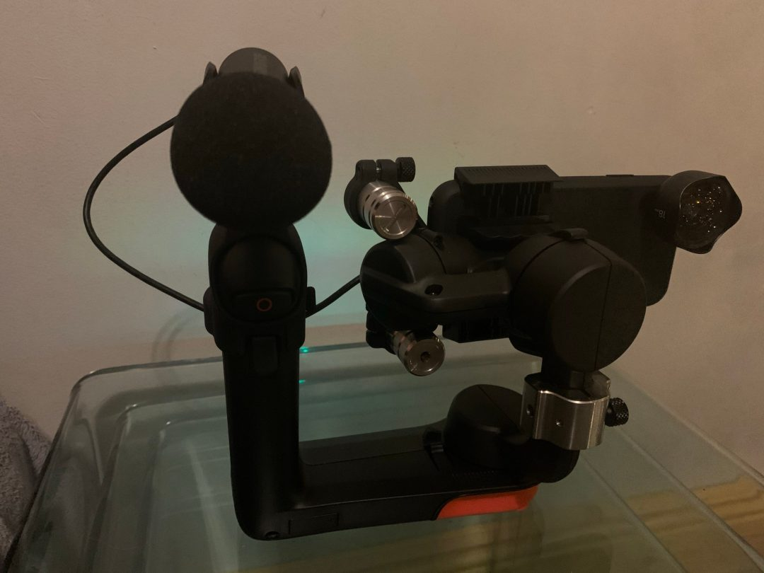 Picture of the iPhone attached to a gimbal with a camera on the top. It looks very professional