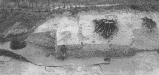 Image 10 - The blocked south-west gate at an early stage in excavation. The figure stands on a soil level which accumulated within the gate after abandonment and before the chalk rubble (behind) was dumped to block the entrance gap. Some cobbling of the early road can be seen. The line of the early road is visible running between the hornworks beyond the fence.