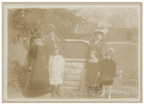 Standing around a Daniel Boone trail marker are (adults) Mrs. Lindsay Patterson, Mrs. William Neal Reynolds, and Miss Edna Maslin, 1914.