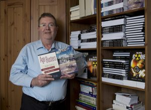 Author Charles Salter in his basement office with shelves filled with books he has written over the years. Staff photo by Bill Green