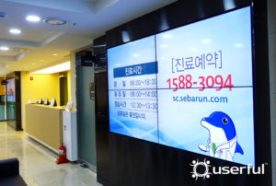 A 2 by 2 grid video wall is displayed in a waiting room of the Seocho Sebarun Hospital