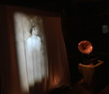 projection of ghostly figure and an old-fashioned record player