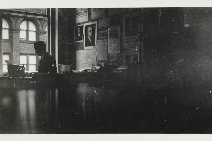 Man in silhouette types in an office - Undated