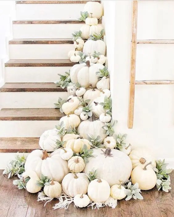 a staircase decorated with lots of white pumpkins, greenery and boho macrame for chic fall decor