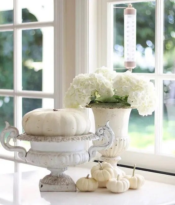 a white fall decoration of vintage urns, white pumpkins and blooms is very elegant and chic