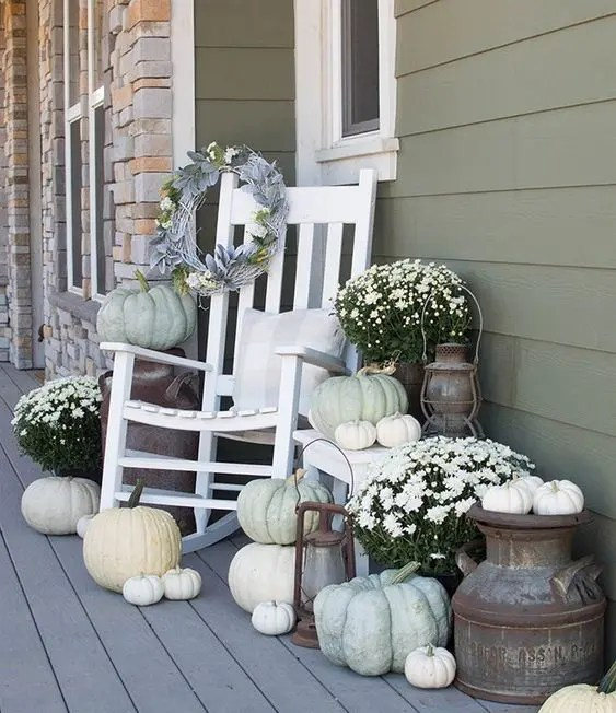 neutral rustic porch decor with white potted blooms, white and neutral pumpkins, white furniture and pillows