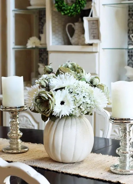 vintage fall centerpiece of white candles and a white pumpkin with white blooms of various kinds