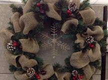 a burlap and evergreen wreath with a rhinestone snowflake, snowy pinecones and cranberries