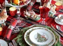 a plaid tablecloth and napkins add a cozy traditional feel to the table, and evergreens make it lively