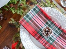 plaid napkins, red ribbons, evergreens and snowy pinecones will make up a gorgeous Christmas table