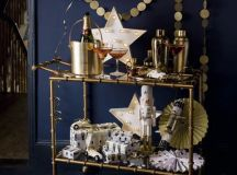 a brass bar cart with a gold garland, a neon star sign, paper fans and a balloon